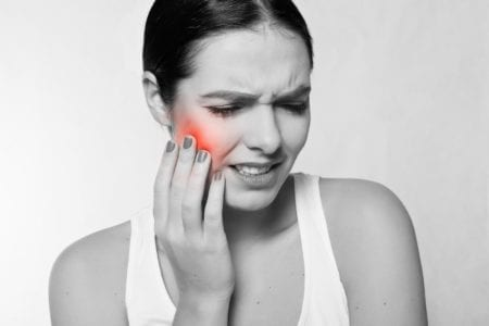 Lady holding her cheek grimacing with obvious mouth pain.