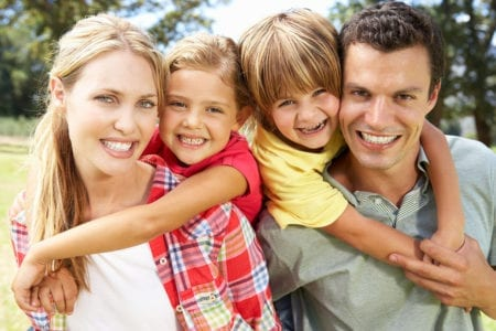 A woman, man, and two young children hugging and smiling at the camera