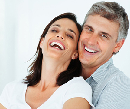 Middle-aged couple smile with their mouths partially open - for information on zirconia crowns