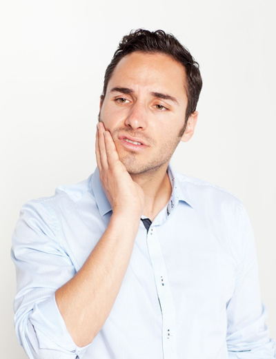 Brunette man holding the side of his face perhaps with a weird sensation in a dental crown or implant